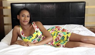 Beautiful black female in hawt dress relaxes on bed