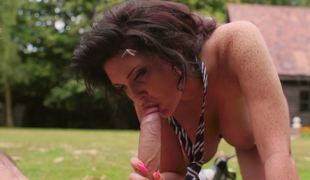 A brunette hair is out in the yard, naked, getting rammed by a man